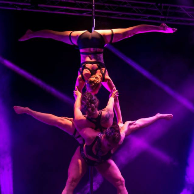 Das Poledance Trio Poley Trinity zeigt die drei Frauen bei ihrer Performance für das Poledance Playhouse. Das Bühnenlicht ist lila-pink-violett.