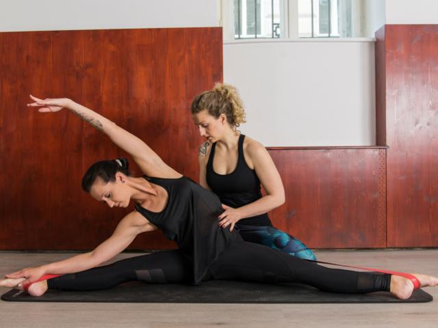 Die Trainerin hilft ihrer Schülerin beim Dehnen und Flexiblerwerden, welche in der Grätsche mithilfe eines Deuserbandes dehnt.