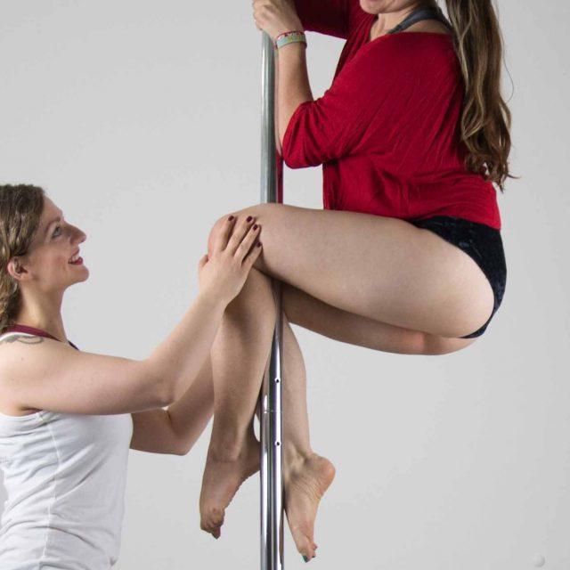 Die Trainerin hält die Knie der Schülerin fest, welche an der Stange sich mit Beinen und Händen festhält. Beide Frauen lächeln sich an und teilen die soeben erlebten Erfolge beim Poledance. Beide sind voller Stolz erfüllt.